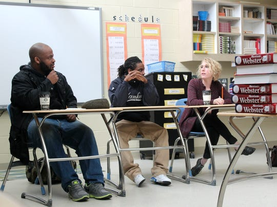 Writer Kiese Laymon, left, visited Tate High School on Friday to talk with students. Student Marquice Williams and University of Iowa adjunct professor Mallory Hellman sit beside him to the right.