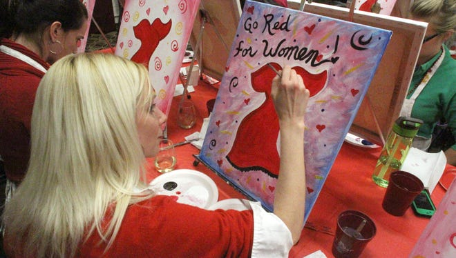 Tara Tomcsik, of Wixom, works her painting during a wine and art session at Brighton's Studio West for Go Red For Women.
