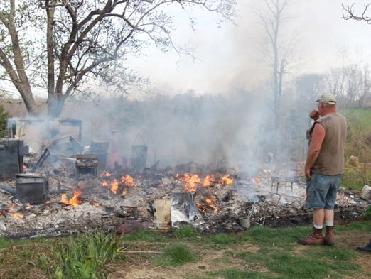 Samuel Fields looks over the smoldering ruins of his mother Hazel's home in Verona.