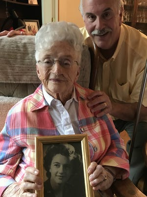 Jean Bearup, 96, shows a portrait of herself as a young nurse. She recalls her days as a WWII nurse in France with her son, Rich, at her home May 25, 2017.