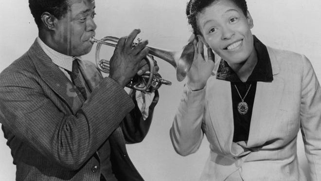 "Billie Holiday, right, gives a listen to Louis Armstrong and his horn as they are appearing in the film ""New Orleans,"" directed by Arthur Lubin."