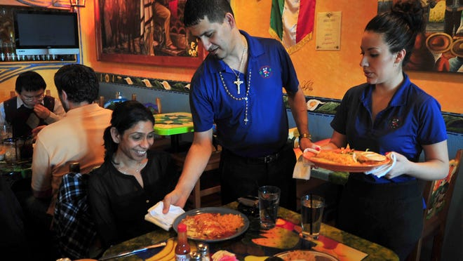Servers Rodrigo Cervantes and Rosa Torres serve luncheon dishes to a table. At left Ritu Jaswal, who works in Whippany, is served a veggie burrito.