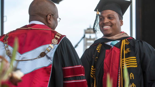 Clarence Banks (right) receives the Presidential Leadership Award from Delaware State University President Dr. Harry L. Williams during graduation ceremonies at Delaware State on Sunday morning.