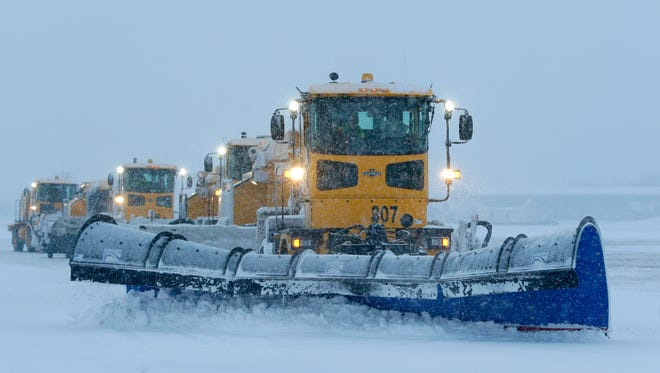 Plows are lined up as they begin snow removal on a runway Monday at Mitchell International Airport.