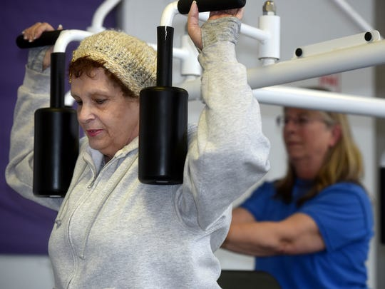 Vie Hall stretches before working out at THE Women's Gym on Wednesday at 404 S. Park Ave. in Aztec.