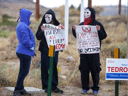Tyrel Sabin, middle, and Jack Downey, right, speak with a woman on the corner of Pinon Hills Boulevard and North Dustin Avenue while protesting a local appearance by Donald Trump Jr. on Friday.