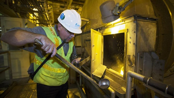 MMSD contract administrator Steve Unger opens an operating dryer inside the Milorganite fertilizer factory on Jones Island in July 2016.