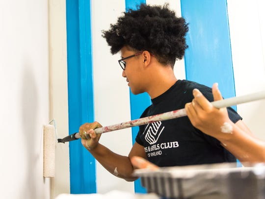 Marcquise Russell, 16, paints a wall in the new Boys