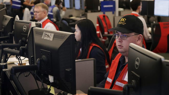 Pacific Gas & Electric employees work in the PG&E Emergency Operations Center in San Francisco in 2019. Pacific Gas and Electric promised regulators Thursday that it has learned from its mishandling of deliberate blackouts and won't disrupt as many people's lives during the pandemic this year, when the utility expects to rely on outages to prevent its outdated grid from starting deadly fires.