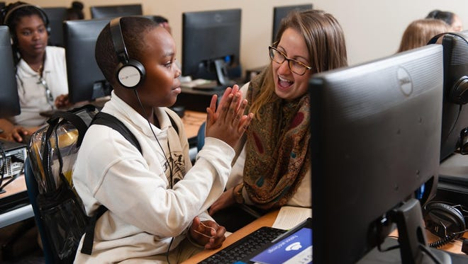 A student gives a high-five to a mentor after a CS First class, Google's program aimed at exposing elementary-age children to computer science. A new poll reveals that while many parents want CS taught in schools, administrators aren't aware of that demand.