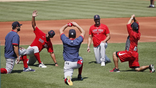 Red Sox players warm up with stretching exercises before practice at Fenway Park on Tuesday. Conspicuous by his absence was Rafael Devers, who was sent to Boston College to work out. The regulars remained at Fenway.
