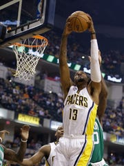 Indiana Pacers' Paul George (13) grabs a rebound during the first half of an NBA basketball game against the Boston Celtics, Wednesday, Nov. 4, 2015, in Indianapolis. (AP Photo/Darron Cummings)