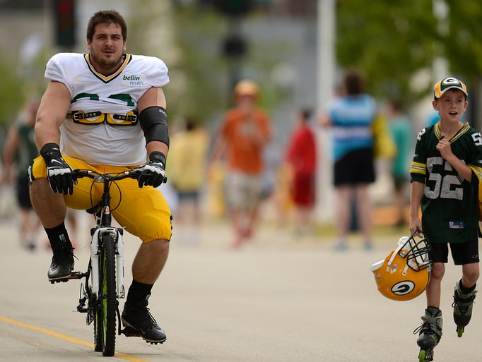 Green Bay Packers center Corey Linsley (63) and Travis Kohlbeck, 10, of Ashwaubenon, ride to training camp practice at Ray Nitschke Field on Monday, Aug. 4, 2014. Evan Siegle/Press-Gazette Media