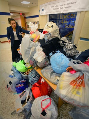 Student ambassador Nevaeh Williams, 10, helps pile some of the donations given by students and attendees at the 2016 MLK America's Sunday Supper at Lincoln Charter School.
