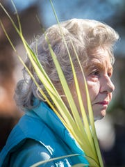 Ruth Clements walks with a palm frond to Christ Church with other members of the congregation as they celebrate Palm Sunday in Dover on Sunday morning.