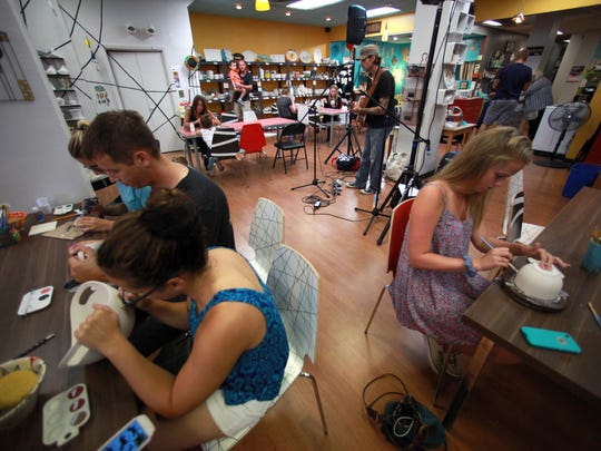 Customers at The Fire paint pottery while Teddy Davenport performs during Mile of Music in downtown Appleton. The Fire was among the unexpected venues showcasing live music at the festival.
