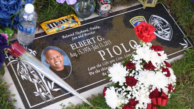 Flowers and other personal items are set atop the headstone of Guam Police Department Sgt. Elbert Piolo at the Our Lady of Peace Memorial Gardens on Thursday, July 13, 2017. Family members and friends visited the officer's grave in observance of the second anniversary of his death, as a result of a shooting incident in Yigo on July 13, 2015.