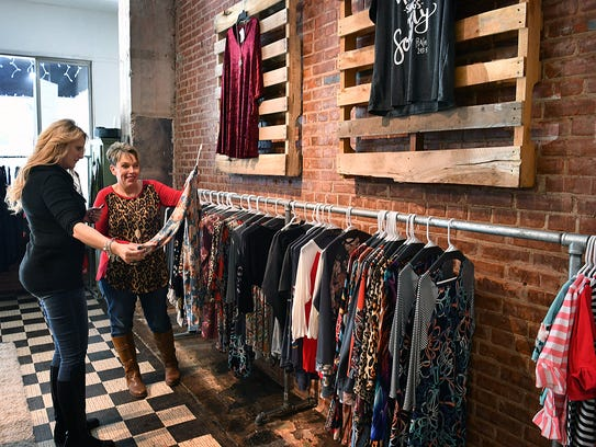 Dodie Robey, owner of Dodie's Closet, helps a customer,
