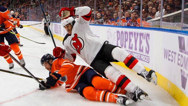 New Jersey Devils' Brian Boyle, top, checks Edmonton Oilers' Eric Gryba (62) during the first period of an NHL hockey game Friday, Nov. 3, 2017, in Edmonton, Alberta. (Jason Franson/The Canadian Press via AP)