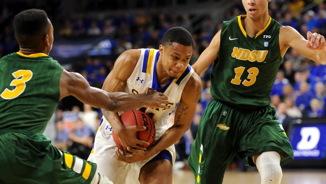 South Dakota State Jackrabbits guard George Marshall (11) drives between North Dakota State Bison guard Carlin Dupree (3) and guard Khy Kabellis (13) during the first half of the Summit Conference tournament.