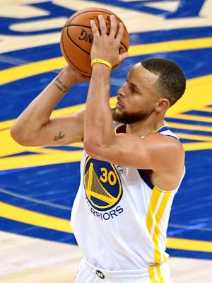 Stephen Curry shoots the ball against Kevin Love during the fourth quarter in Game 1.