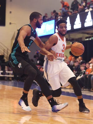The Westchester Knicks' Chasson Randle, right, takes the ball down the court as the Greensboro Swarm's Aaron Harrison, left, defends during the Knicks' home opener.
