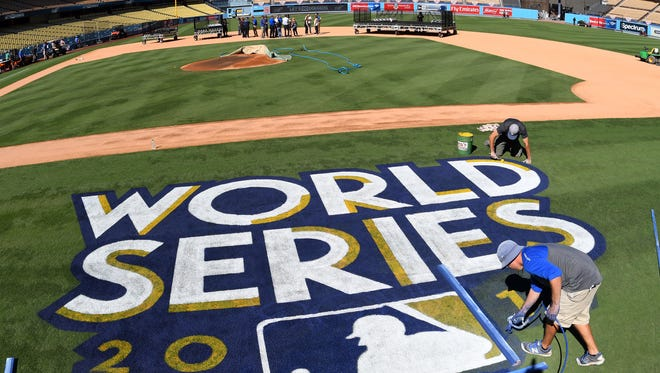 Oct. 23: Media Day/Workout at Dodger Stadium - Painters put the finishing touches on the World Series logo and the field before Monday's workouts at Dodger Stadium.