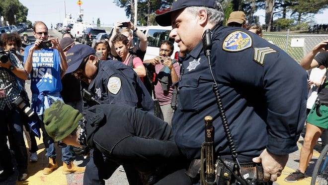 San Francisco Police officers arrest a protester outside of Alamo Square Park in San Francisco on Saturday, Aug. 26, 2017.