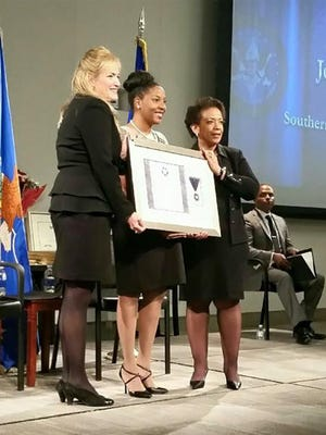 Josie Wells wife, Channing, (center) accepts a Purple Heart from U.S. Marshals Service Director Stacia Hylton (left) and U.S. Attorney General Loretta Lynch (right).