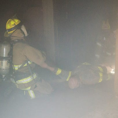 """Firefighters locate and remove a """"victim"""" from the"""
