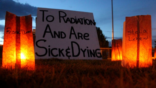 """In this file photo from July, signs reading """"We are American citizens who lived in the area surrounding the Trinity Site and were overexposed to radiation and are sick and dying"""" were placed behind 700 luminarias on a baseball field in Tularosa. The memorial was set up as part of the Tularosa Basin Downwinders' 7th annual candlelight vigil."""