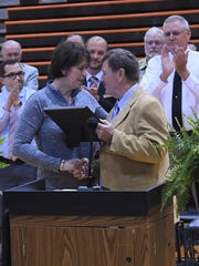 Connie Moser shakes hands with Rural Education Association executive director Dale Query on Friday. Moser, Calico Rock's special education supervisor, was selected as the REA's Teacher of the Year.