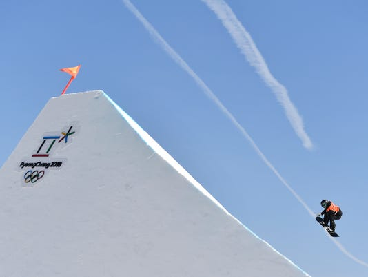 A snowboarder flies through the air during a women slopestyle training session at the Phoenix Snow Park ahead of the 2018 Winter Olympics in Pyeongchang, South Korea. Wednesday, Feb. 7, 2018. (Michal Kamaryt/CTK via AP)