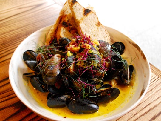 Mussels steamed in saffron-rich broth with grilled