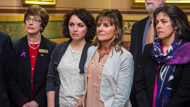 Melissa Zebrowski, center left, and Jeanette Birch stand together after discussing the loss of loved ones who overdosed on opioids during a news conference to commemorate Opioid Overdose Awareness Day at the Statehouse in Montpelier on Thursday, April 13, 2017.