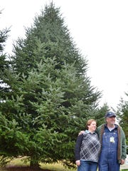 Mary and David Vander Velden of Oconto, owners of Whispering Pines Tree Farm, stand by the fir tree on Tuesday that was cut down to be shipped to the White House as the Official White House Christmas Tree.