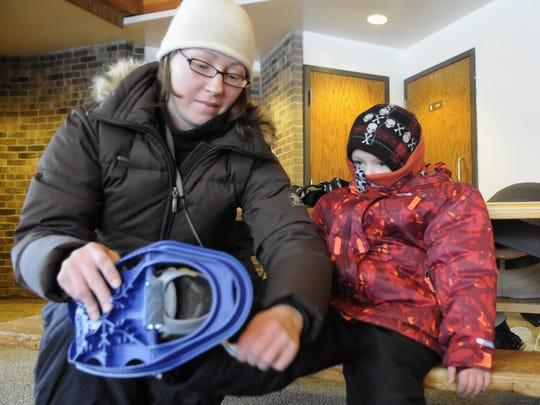 Jessica Harding of Zimmerman helps her son Atticus strap on showshoes during Lake Maria State Park's Winter Fun Day in 2013.