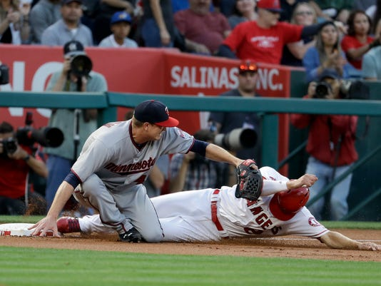 Los Angeles Angels' Andrelton Simmons, right, is tagged out by Minnesota Twins starting pitcher Kyle Gibson while trying to advance on a ball hit by Kole Calhoun during the first inning of a baseball game in Anaheim, Calif., Friday, June 2, 2017. (AP Photo/Chris Carlson)