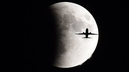 A plane flies in front of a so-called supermoon during a lunar eclipse Sunday, Sept 27, 2015 in Geneva, Ill. It was the first time that the events made a twin appearance since 1982, and they won't again until 2033. (Jeff Knox/Daily Herald via AP) MANDATORY CREDIT; MAGS OUT