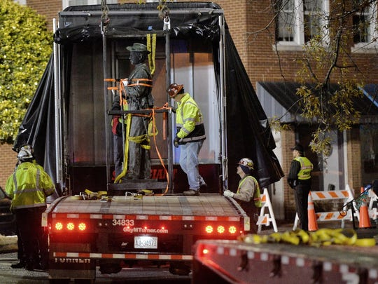 Workers load a Confederate statue onto a truck after it was removed from its spot in front of the historic Chatham County courthouse in Pittsboro, N.C.