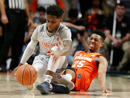 Miami guard Chris Lykes (2) regains control of the ball against Syracuse guard Tyus Battle (25) during the second half of an NCAA college basketball game, Saturday, Feb. 17, 2018, in Coral Gables, Fla. Syracuse defeated Miami 62-55. (AP Photo/Wilfredo Lee)