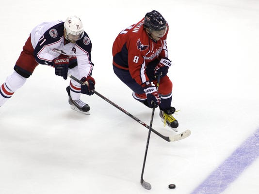 Washington Capitals' Alex Ovechkin (8), of Russia, moves the puck as Columbus Blue Jackets'  Nick Foligno (71) defends during the second period of an NHL hockey game, Tuesday, Nov. 11, 2014, in Washington. (AP Photo/Luis M. Alvarez)