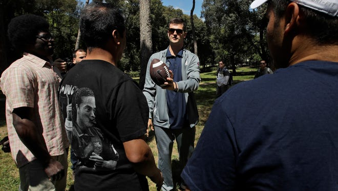 Michigan quarterback Wilton Speight teaches refugees how to throw a football on Sunday at the Borghese Gardens.