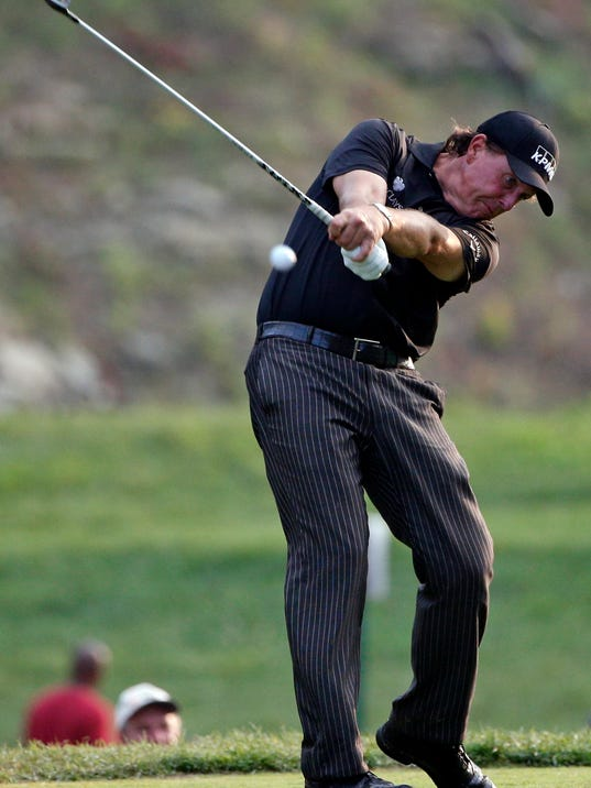 Phil Mickelson hits his tee shot on the 15th hole during the final round of the PGA Championship golf tournament at Valhalla Golf Club on Sunday, Aug. 10, 2014, in Louisville, Ky. (AP Photo/Mike Groll)