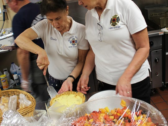 Claudia McClenny and Karen Lett slice a quiche at the 2014 Bethany Artisan's Festival.