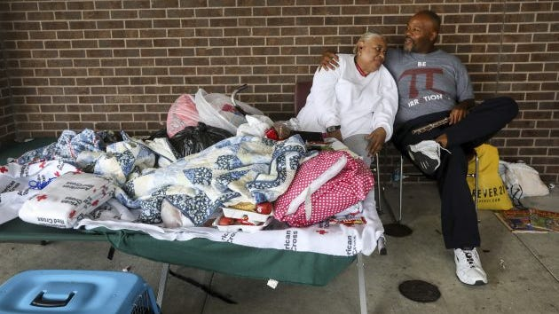"""James Ward, right, a music student at Sam Houston State University, attempts to make Vivian Williams smile at a Red Cross shelter at W. W. Thorne Stadium in Houston, Aug. 29, 2017. Ward, who lived through Hurricane Katrina, said, """"We've been blessed, people need smiles."""""""