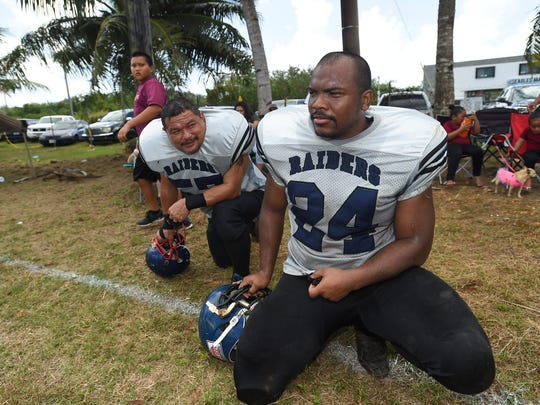 Raiders players take rests during a Budweiser Guahan Varsity Football League game at Eagles Field on Feb. 17, 2018.