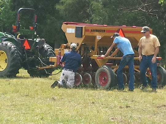 Rep. Jay Reedy, right, helps prepare no-till drill