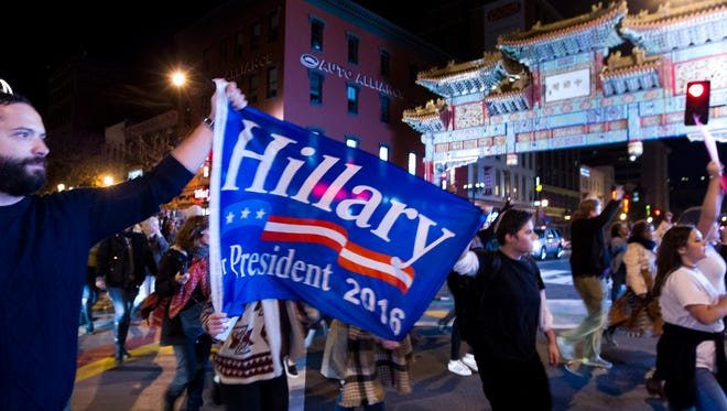 A protester holds a banner supporting Hillary Clinton for president during a march in downtown Washington in opposition of President-elect, Donald Trump on Nov. 12, 2016.
