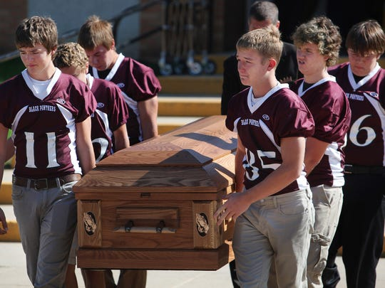Casket bearers Payton Foxley (11) and Trevor Sprik  (85) along with other members of the Platte-Geddes football team carry the casket of their friend, Michael Westerhuis, outside of the Platte-Geddes Elementary School on Sat., Sept., 26, 2015 after the funeral service held in memory of the four Westerhuis children that died last week.